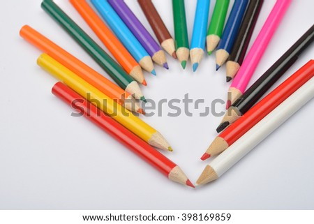 Close up picture of colored pencil crayons arranged in shape of heart on white background. Assortment of colored pencils/ Colored drawing pencils. Selective focus - stock photo
