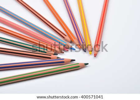 Close up picture of colored pencil crayons with stripes on white background. Assortment of colored pencils/ Colored drawing pencils. Selective focus - stock photo