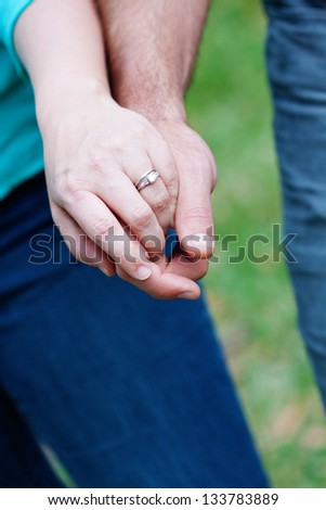 Close up picture of holding hands and engagement ring