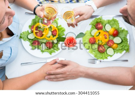 Close-up picture of lunch table. Happy mature couple drinking champagne outdoor,s laughing and enjoying wedding day. - stock photo