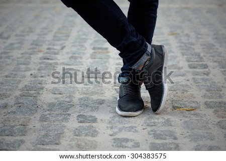 Close-up picture of man who crossed his legs. Man in black jeans and sneakers enjoying daytime in the city. - stock photo