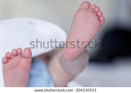 Close up picture of new born baby feet on a white sheet - stock photo