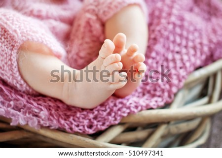 Close up picture of newborn baby feet in knitted plaid