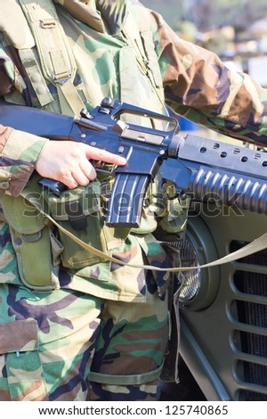 Close-up picture of soldier with a gun in hand. - stock photo