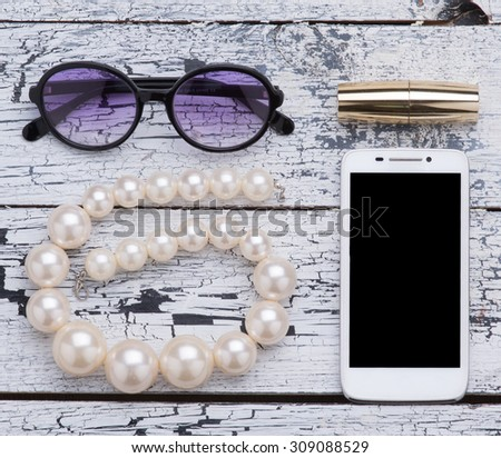 Close-up picture of summer objects to spend vacations' evenings. Smart phone, sunglasses, lipstick and beads are represented on white wooden. - stock photo