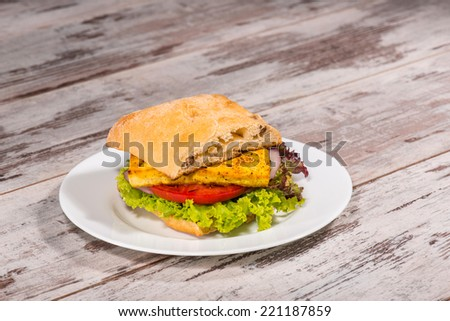Close-up picture of vegetarian sandwich with tofu, tomatoes, salad and cucumber on the white plate standing on the wooden table in vegan caffee, with copy place - stock photo