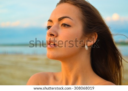 Close up picture of young brunette sensual  pensive lady on beach by sea at sunset - stock photo