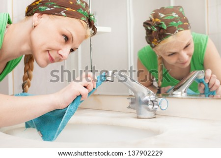 close up picture of young woman cleaning the tap.tap is in focus - stock photo