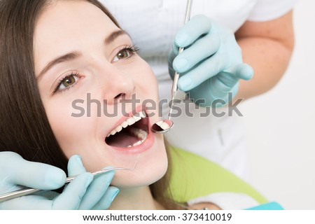Close-up picture of young woman sitting in the dentist's chair with opened mouth at dentist's office while having examination.