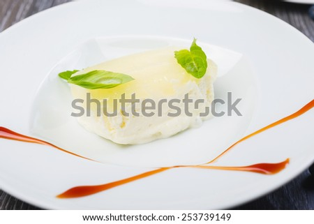 close up piece of Creamy vanilla ice cream with jelly and mint leaves on a white plate on a wooden table with decor and tea - stock photo