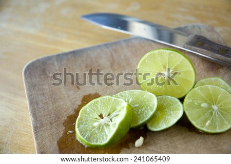 close up pieces of lime on wooden cutting board - stock photo