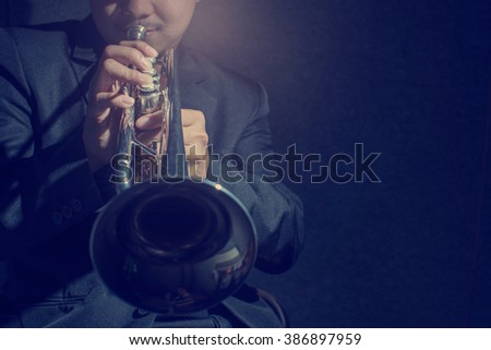 Close up Pipes in the hands of trumpet player on dark,low key and retro image - stock photo