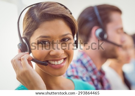 Close up plan of a smiling businesswoman in a call centre - stock photo