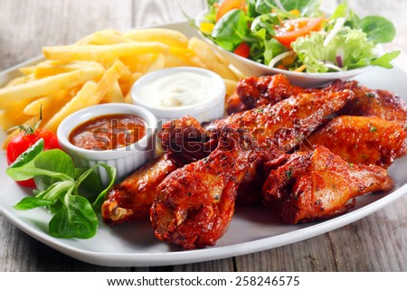 Close up Plate for Main Entree with Crispy Fried Chicken Drumsticks Paired with Potato Fries, Veggies and Homemade Gravy, Served on Wooden Table. - stock photo
