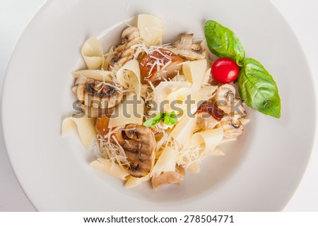 Close up Plate of  delicious Pasta with mix of mushrooms and cheeses with cream decoratred with cherry tomatos and basil on the white plate isolated - stock photo