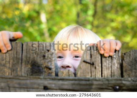 Close up Playful Little Blond Girl Peeking on Old Wooden Fence at the Garden - stock photo