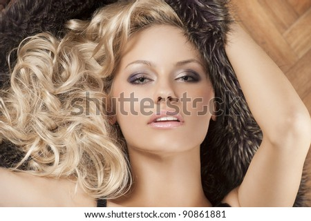 close up portarit of young  alluring beautiful girl with blond curly hair wearing a black bra with fur around her - stock photo