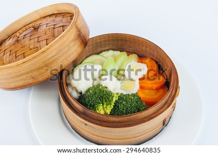Close up Portion of steamed vegetables: broccoli, cauliflower, zucchini, celery, carrots in a wood tray on the white background isolated - stock photo