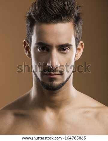 Close-up portrait a of a handsome young man looking to the camera - stock photo