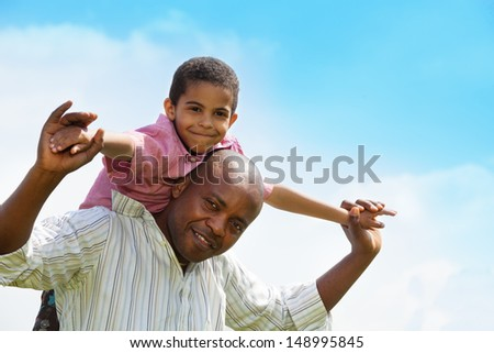 Close-up portrait African American father and the sun playing together - stock photo