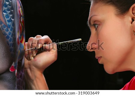 close-up portrait artist's, perform body painting koi fish on a black background studio