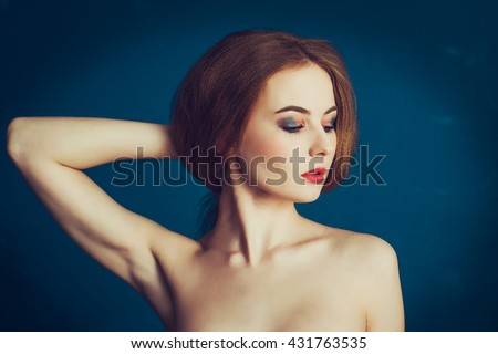 Close-up portrait beautiful girl on a blue background. Woman showing her armpits - stock photo