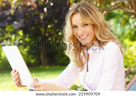 Close-up portrait beautiful mature woman sitting at garden while holding digital tablet.  - stock photo