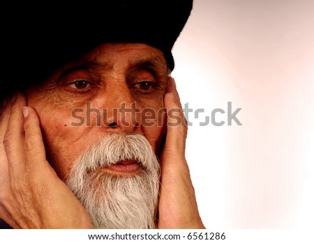 close up portrait elderly male with hands on face eyes looking right across frame. - stock photo