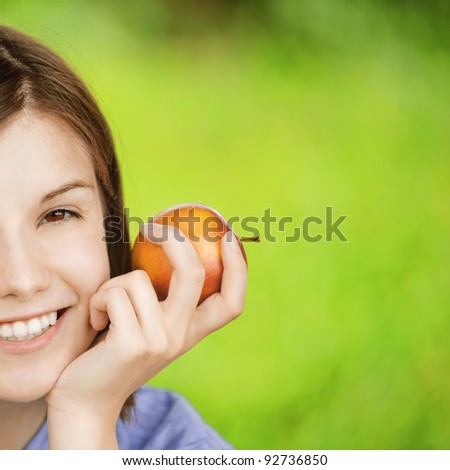 Close-up portrait half of young smiling brunette woman holding red apple at summer green park. - stock photo