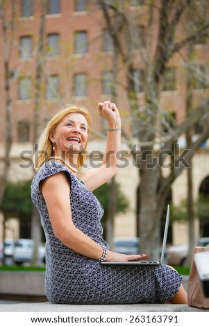 Close Up portrait, Happy and Smiling old senior business woman 60-65 years, using laptop computer on your lap in New York city park, looking to up, with gesture on face, emotions raised hand up