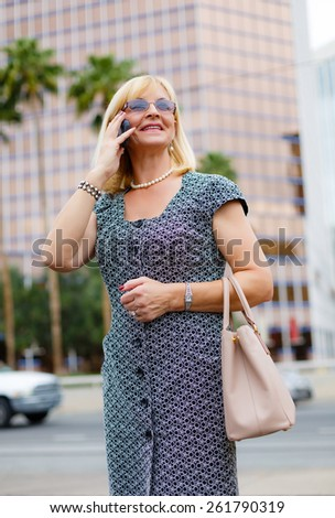 Close Up portrait happy smiling attractive business woman in glasses 60 years in the downtown talking with mobile phone, Lifestyle woman on phone, business woman calling on the phone in street - stock photo