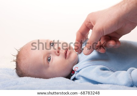 Close-up portrait if newborn baby lying so serious and looking at his father. Newborn baby and father's hand. Little baby lying on blue towel.