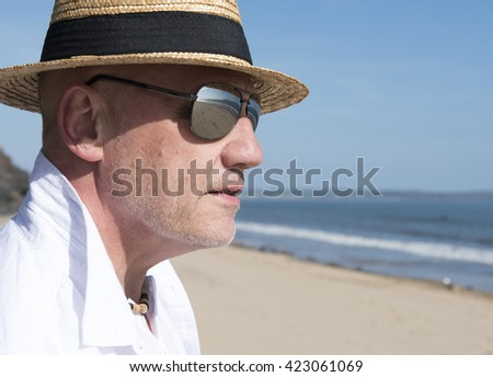 Close up portrait image of a mature man on the beach wearing a hat and sunglasses. You can see reflections of the beach in his glasses.