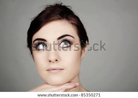 close up portrait image of a young woman in a grey dress - stock photo