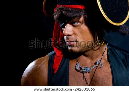 Close-up portrait muscular pirate in the studio on a dark background. Man looking away - stock photo