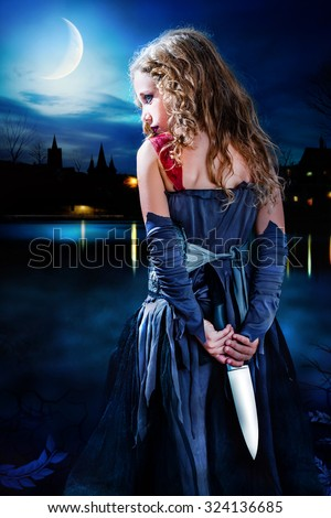 Close up portrait mysterious Gothic girl holding knife behind back. Girl standing with big knife behind back at dusk. Medieval city skyline in background with reflection on dark water.