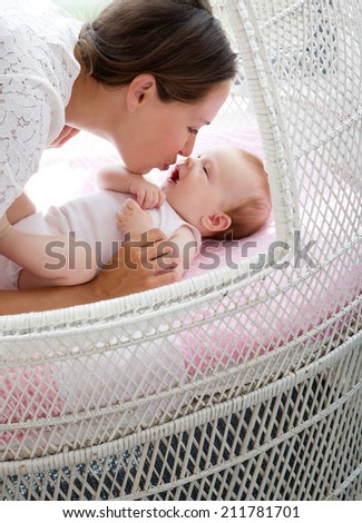 Close up portrait o f a loving mother kissing baby in bed - stock photo