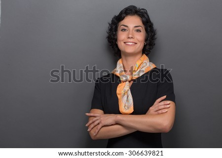 Close-up portrait od air stewardess isolated on grey. Smiling adult lady in black dress and yellow neckcloth posing with her arms crossed. - stock photo