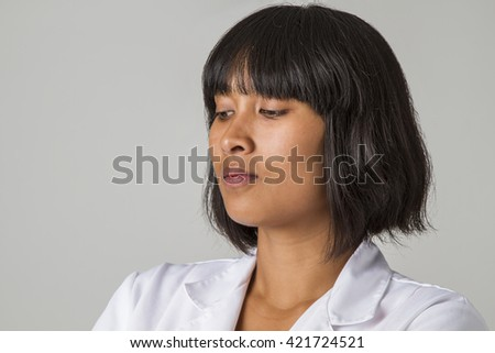 Close up portrait of a asian doctor looking down - stock photo
