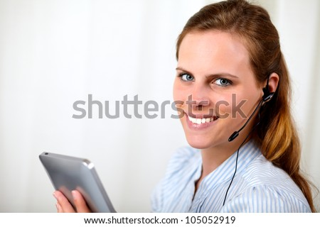 Close up portrait of a attractive blonde secretary smiling on callcenter with a tablet PC at customer service office