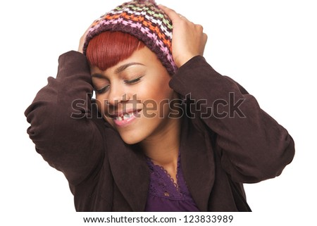 Close up portrait of a beautiful African American girl smiling and happy. She has her hands to her head and is wearing a fashionable winter hat. - stock photo
