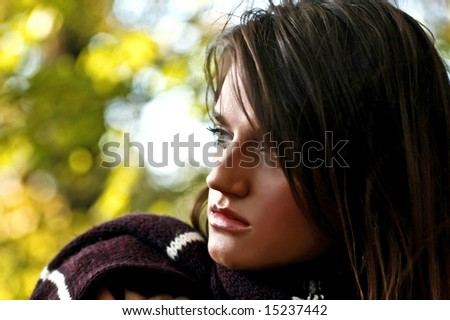 Close up portrait of a beautiful and thoughtful young girl. Outdoor background - stock photo