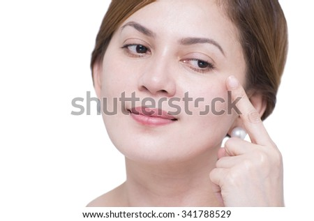 Close up portrait of a beautiful asian lady checking for eyebags and wrinkles. isolated in white background.