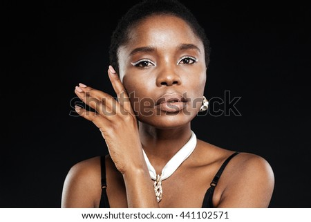 Close-up portrait of a beautiful attractive ethnic african woman isolated on the black background - stock photo