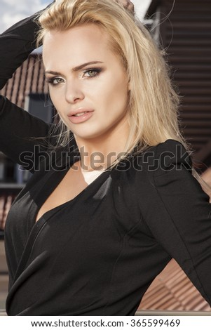 Close up portrait of a beautiful attractive slim sexy and sensuality young adult pretty blonde woman in elegance black dress on the morning sunlight balcony - stock photo