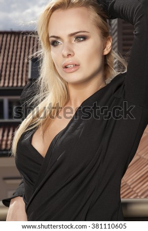 Close up portrait of a beautiful attractive slim sexy and sensuality young adult pretty blonde woman in elegance black dress on the morning sunlight balcony