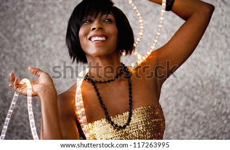Close up portrait of a beautiful black woman holding Christmas fairy lights around her neck and smiling against a silver glitter background. - stock photo