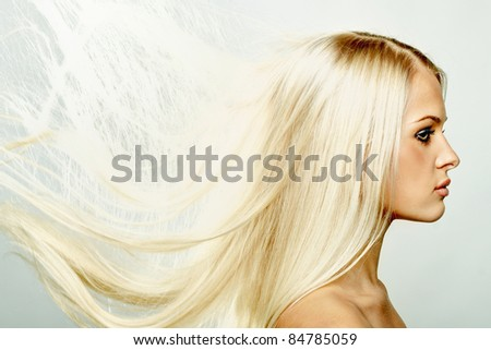 Close up portrait of a beautiful blond female with hair fluttering in the wind - stock photo