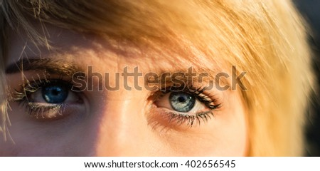 Close-up portrait of a beautiful blonde caucasian woman with blue eyes, looking at camera - stock photo