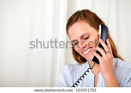Close up portrait of a beautiful blonde girl smiling and speaking on phone